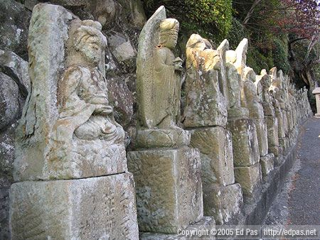 a long row of statues along the driveway up to Amida-in