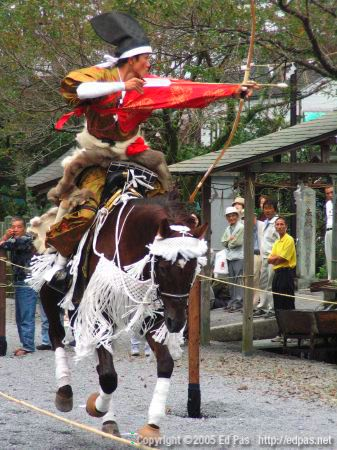 a horse-mounted archer aims at a target (closeup)