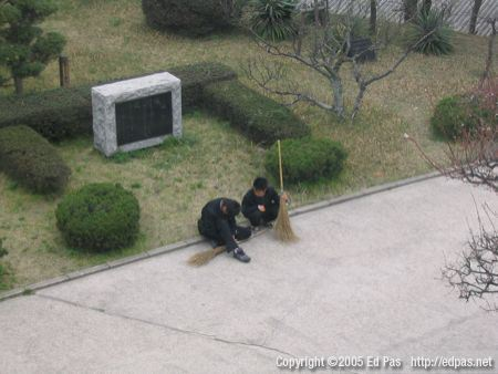 photo of two boys resting in the school courtyard with their brooms