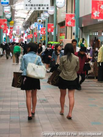 a view of the backs of two women walking through the Kokura arcades