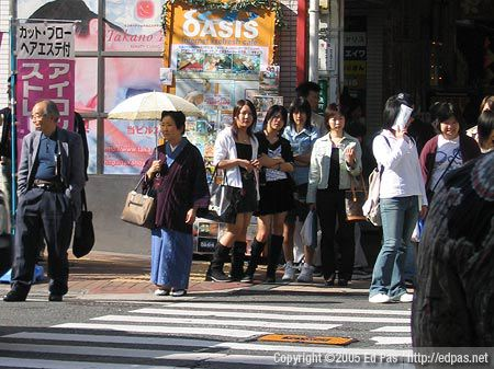 a parasol-toting woman in a kimono, some teenage girls, and others wait at a crosswalk in Kokura