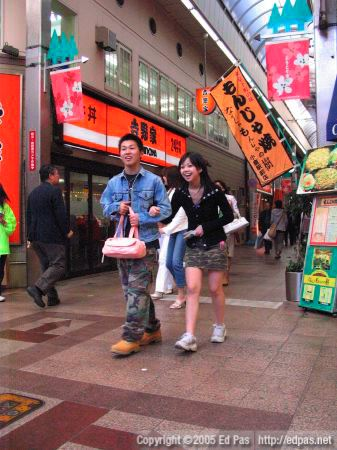 a young camo-wearing couple walking through the intersection in front of Crown Milan bakery in the Kokura arcades