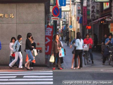 shoppers making their way past people waiting to cross a street in Kokura