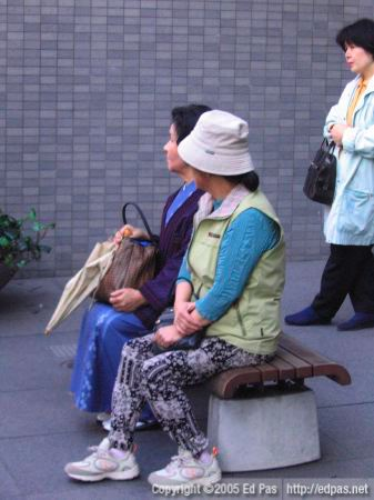 a couple of ladies sitting at the bus stop in front of Fukuoka Bank