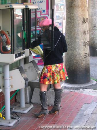 woman in eclectic clothing, using a phone book in front of Lawson in Kokura