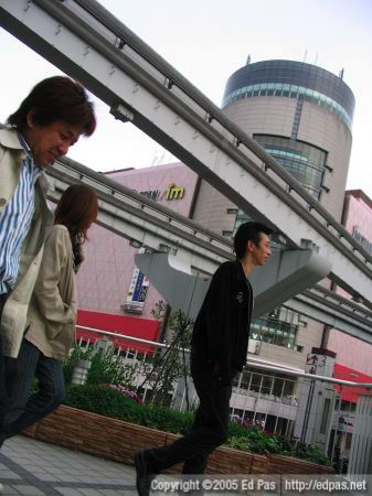 black-clad man with Isetan and monorail tracks in the background