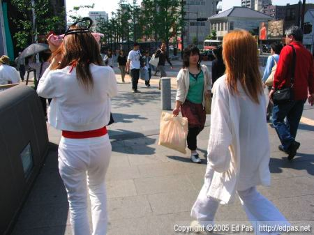 a couple in white, the woman on the left is shielding her face from the sun with her handbag