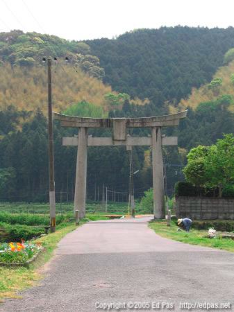 photo of the main torii of Nishi Ono Hachimangu, with farming lady starting a fire in the field in front of it