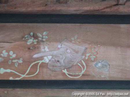 faded painting above the rear beam, inside the front building of Nishi Ono Hachimangu, of a long-nosed mask