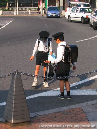 two schoolboys stomping a bug in front of Tobata Station