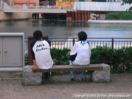 photo of a couple sitting on a bench in the park overlooking the Murasaki River in Kitakyushu