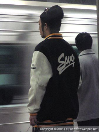 young man in SWG bomber jacket, on train platform at Hakata Station